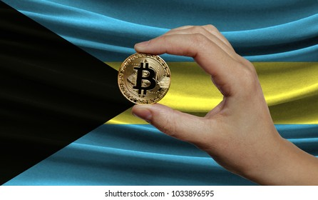 Hand of a man with a gold bitcone Cryptocurrency Digital bit of coins in a hand on a background of the flag of Bahamas.