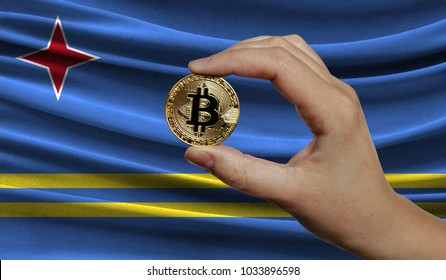 Hand of a man with a gold bitcone Cryptocurrency Digital bit of coins in a hand on a background of the flag of Aruba.
