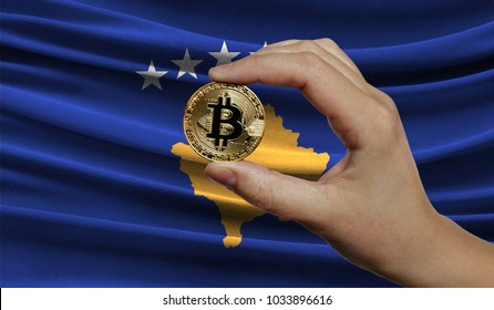 Hand of a man with a gold bitcone Cryptocurrency Digital bit of coins in a hand on a background of the flag of Kosovo.