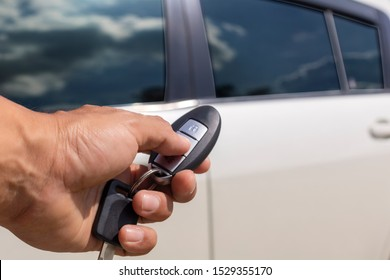 Hand man hold button unlock on the car remote control for unlock door white car.