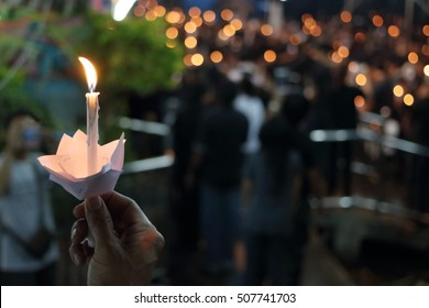 Hand of man hold candle flame light at night with bokeh background