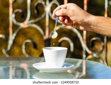 Hand of man hold coffee spoon, or coffe cup. Cappuccino and black espresso coffe cup. Coffee drink. Close up of a man hands holding a hot coffe cups. Closeup. Coffe time, spoon. Black coffee.