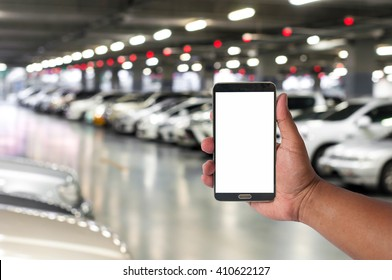 hand of man hold mobile phone over blurred car parking with bokeh light Background