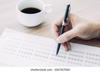 Hand of man holding ballpoint pen and answering questionary form. Male student sitting at table and writing test