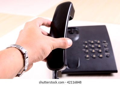 Hand of man holding up a black phone