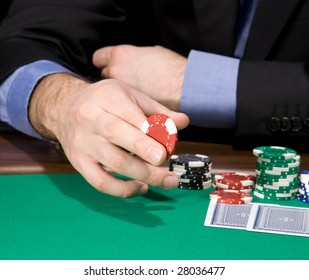 Hand of man holding casino chip over green felt