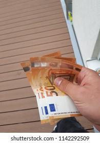 Hand of a man holding Euros banknotes. Cash 50 Euro banknotes.