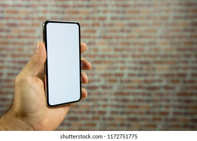 Hand of a man holding a full screen phone in front of a brick wall. white screen for video, copy space.