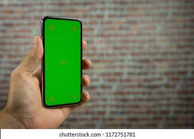 Hand of a man holding a full screen phone in front of a brick wall. Green screen for video, copy space.