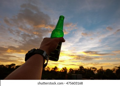 Hand of man holding a green beer bottle on the sunset sky