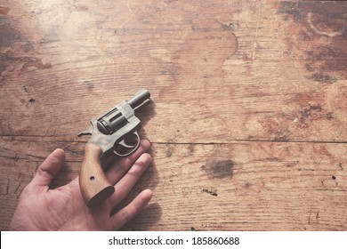 The hand of a man is holding a gun at a wood table