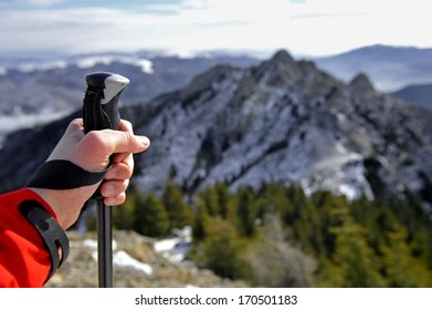 Hand of a man holding a hiking pole on top of a mountain