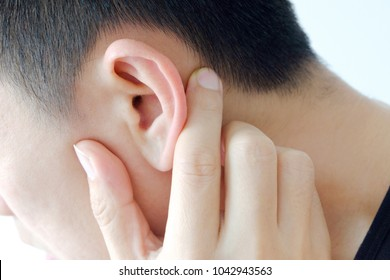 Hand of Man holding his ear because he is earache, Source of pan is acute otiti disease.