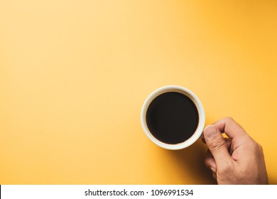 Hand of a man holding a hot black coffee cup on yellow background