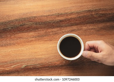 Hand of a man holding a hot black coffee cup on wooden table