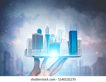 Hand of a man holding a modern city hologram against a night city background. Concept of business and architecture. Toned image double exposure. Elements of this image furnished by NASA