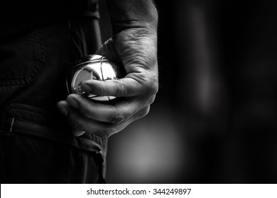 Hand of man holding petanque ball or boule, black and white, artistic