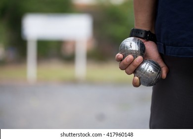 Hand of man holding petanque ball or boule