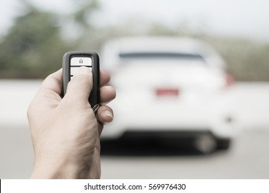 Hand of man holding and push remote control of car and white car parking background technology transportation safety concept