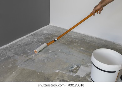 The hand of a man holding a roller and puts primer on concrete floor