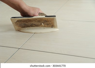 The hand of man holding a rubber float and filling joints with grout