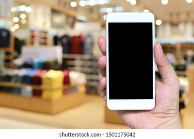Hand of a man holding smartphone device in the blur Shopping mall background and have white copy space on screen.