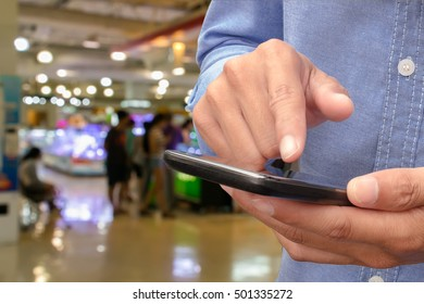 Hand man holding smartphone on blurred of people test mobile phone shop at shopping center