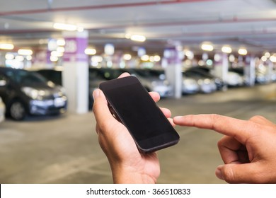Hand of a man holding a smartphone and touching the screen.Parking lot