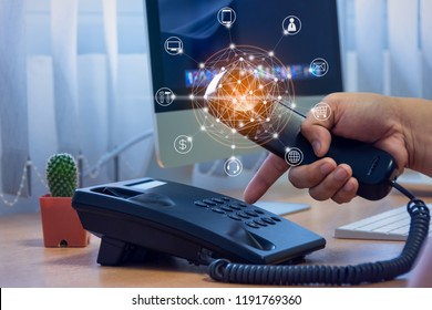 Hand of man holding telephone handset and pressing button on keypad, office desk with cactus pot, computer background, ip telephony services concept with flying icon and connectivity