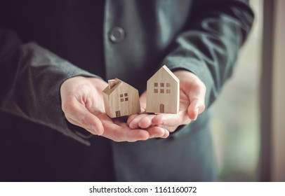 Hand of man holding a toy house. Home safety , Home care , Home for sale concept.