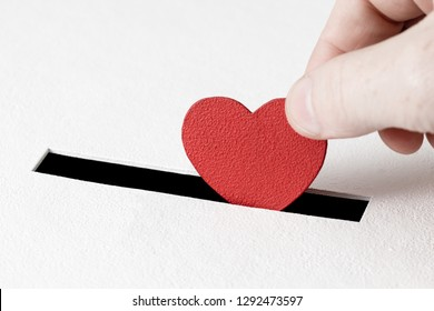 Hand of man inserts heart symbol into hole in donation box on white background with copy space. Concept of donor, life-saving or kindness