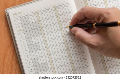 Hand of man marking in open notebook with year plan, holidays planning, work planning