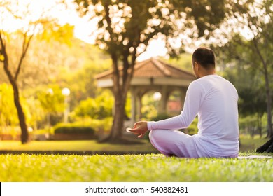 Hand of a man meditating in lotus position practicing yoga outside in park