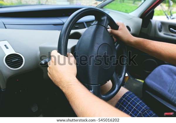 Hand of man on the steering wheel of minivan that travels on city road on sunny summer day. Confident driver behind the wheel.