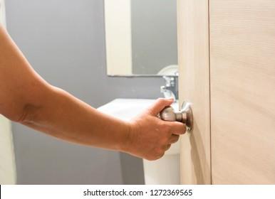 Hand man open the door bathroom