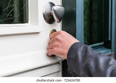 Hand of a man opening front door with key