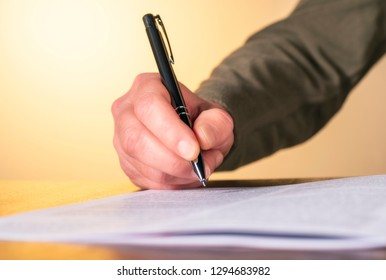 Hand of a man with pen while inspecting a document