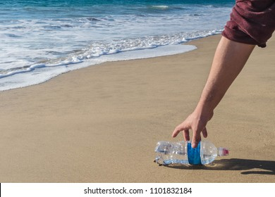 Hand man picking up plastic bottle cleaning on the beach. Volunteer concept.