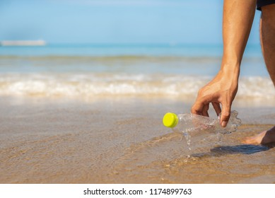 Hand man picking up plastic bottle cleaning on the beach , volunteer and enviroment concept,copy space.