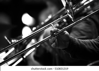 Hand of man playing the trombone in black and white