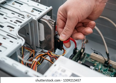 Hand of man plugging SATA (Serial AT Attachment, Serial ATA) data cable in hard drive device. Computer bus interface to connect mass storage devices, close up view.