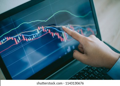 Hand of man point  to the laptop show financial market chart graphic going down.  Stock market concept.
