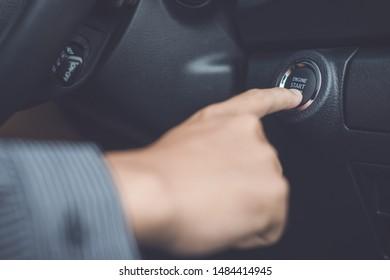 Hand of man pressing button start/stop car engine inside the modern car. Transportation concept