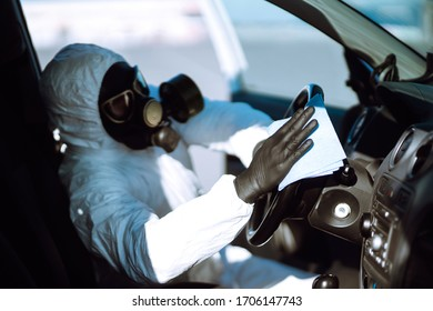Hand of Man in protective suit washing and disinfection of the steering wheel in the car,  prevent infection of Covid-19 virus, contamination of germs or bacteria.