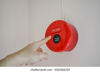 The hand of man is push fire alarm on the wall for safety.