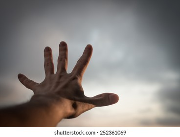 Hand of a man reaching to towards sky with retro filter effect.
