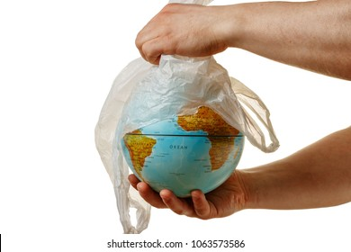 Hand man removes a plastic bag from the globe. World environment day concert. The symbol of the purification of the planet earth from dangerous toxic plastic trash. Isolated white background