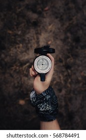 Hand of man with a scarf, holding older metal compass with arrow pointing west. Background is out of focus with coniferous forest environment.