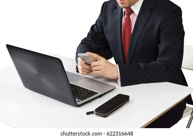 the hand of a man seated at a desk with laptop, telephone and accessories