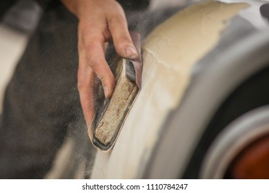 A hand of a man is seen sanding an old vintage car using a block of wood and brown sand grit paper. Manual dry sanding of a car in restoration, a process where putty is removed from bodywork.